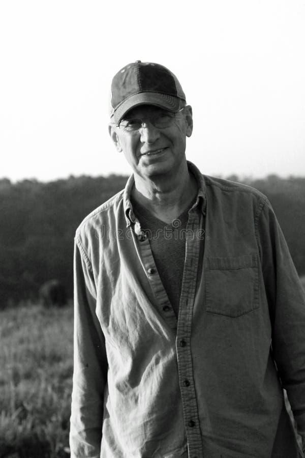 Uomo caucasico più anziano bello sorridente con i vetri nel campo dell'azienda agricola con gli alberi fotografie stock libere da diritti
