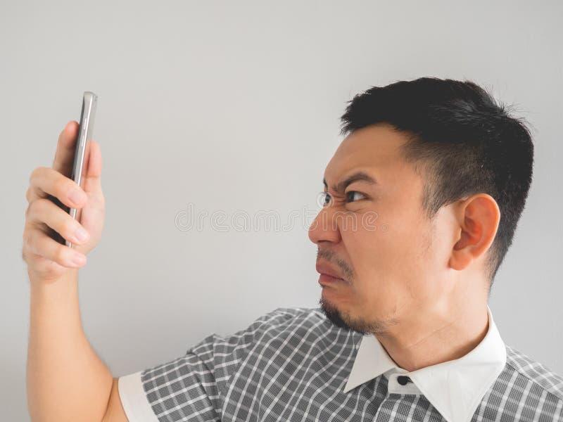 Uomo che è gridato dallo smartphone immagine stock libera da diritti
