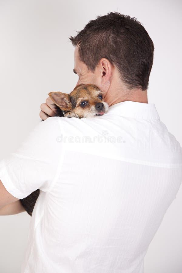 Uomo che abbraccia cucciolo sveglio fotografia stock libera da diritti