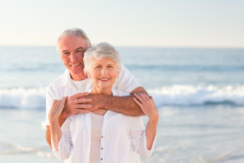 Uomo che abbraccia la sua moglie sulla spiaggia immagine stock libera da diritti