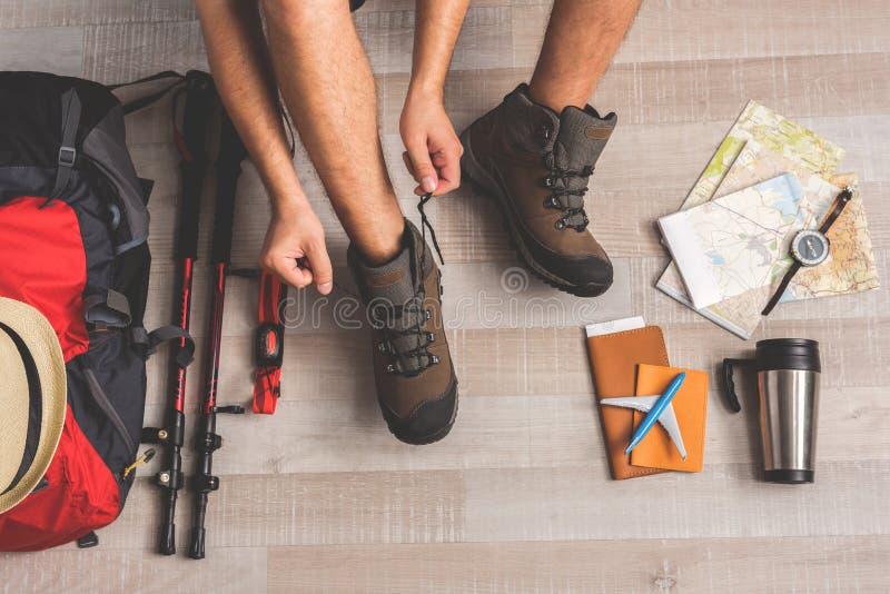Uomo che allaccia i suoi stivali per il viaggio amping fotografie stock