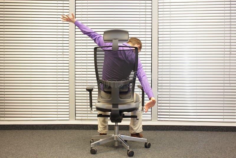 Ufficio Disegno Yoga : Uomo che allunga i braccioli che si siedono sulla sedia in ufficio