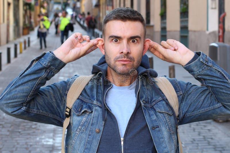 Uomo che allunga le sue orecchie all'aperto fotografie stock libere da diritti