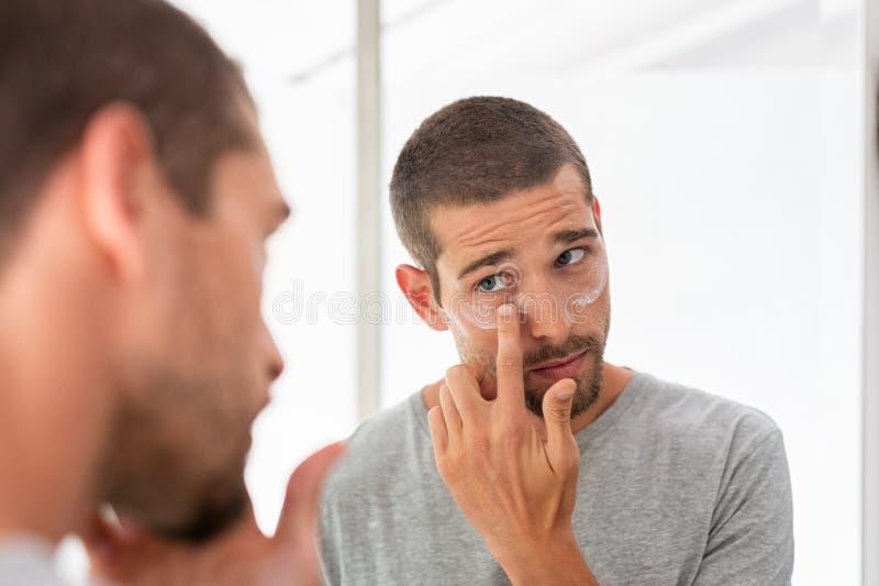 Uomo che applica idratante sotto gli occhi fotografia stock libera da diritti