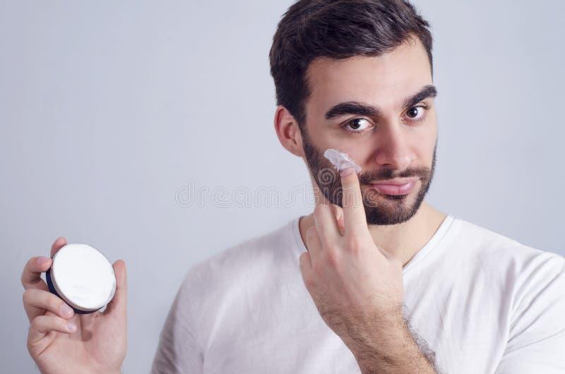 Uomo che applica la crema di fronte sulle guance fotografie stock libere da diritti