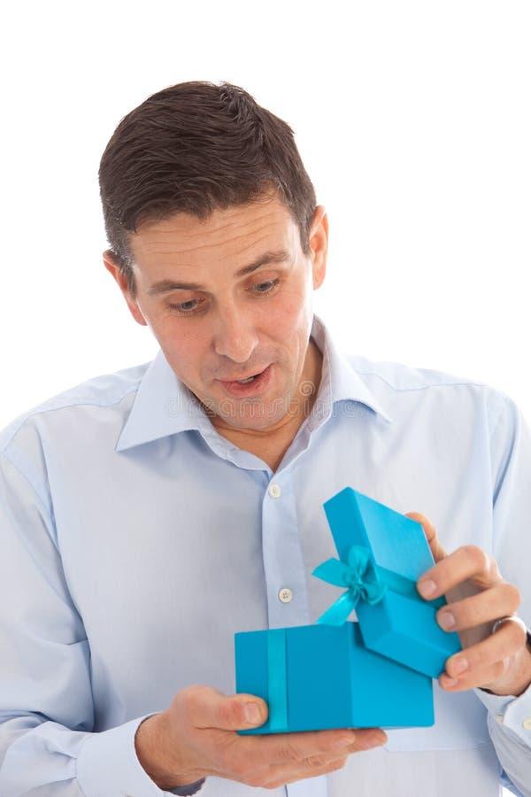 Uomo che apre un regalo di sorpresa fotografia stock