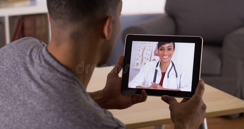Uomo che ascolta medico sulla compressa fotografia stock libera da diritti