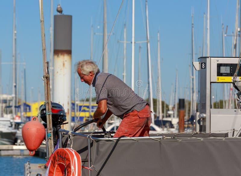 Uomo che aspetta al porto della pompa di olio fotografia stock