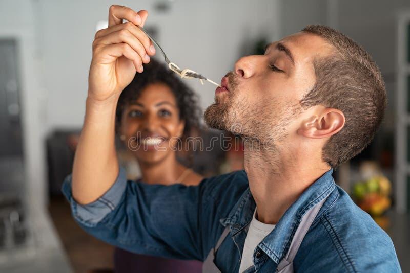 Uomo che assaggia gli spaghetti immagine stock