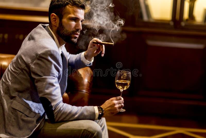 Uomo che assaggia vino bianco e che fuma sigaro immagine stock