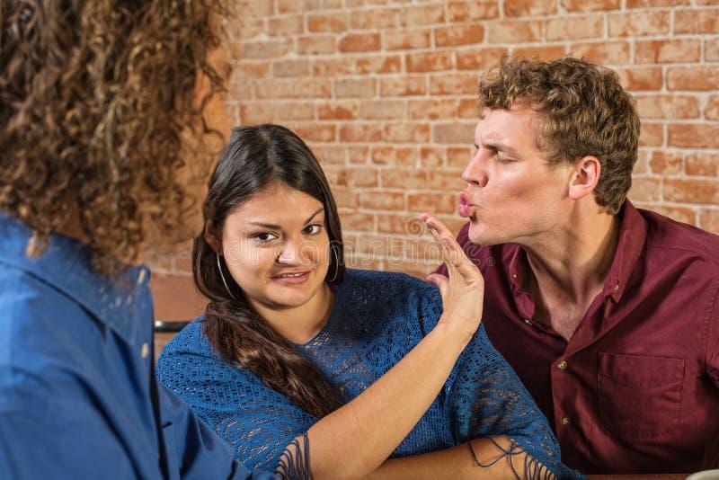 Uomo che bacia donna infastidita immagine stock libera da diritti