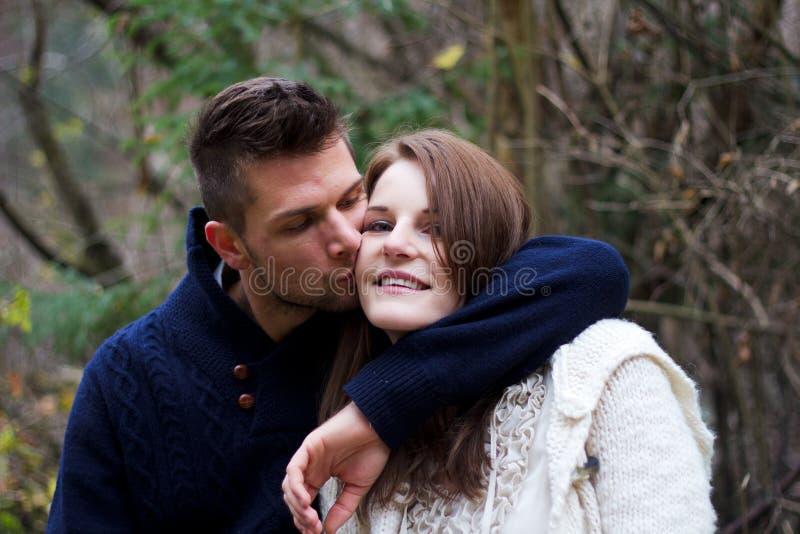 Uomo che bacia donna sulla guancica fotografie stock
