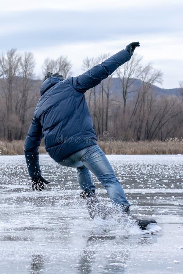 Uomo che cade pattinaggio su ghiaccio di attimo Pattini della neve dallo spargimento nei partiti immagine stock libera da diritti