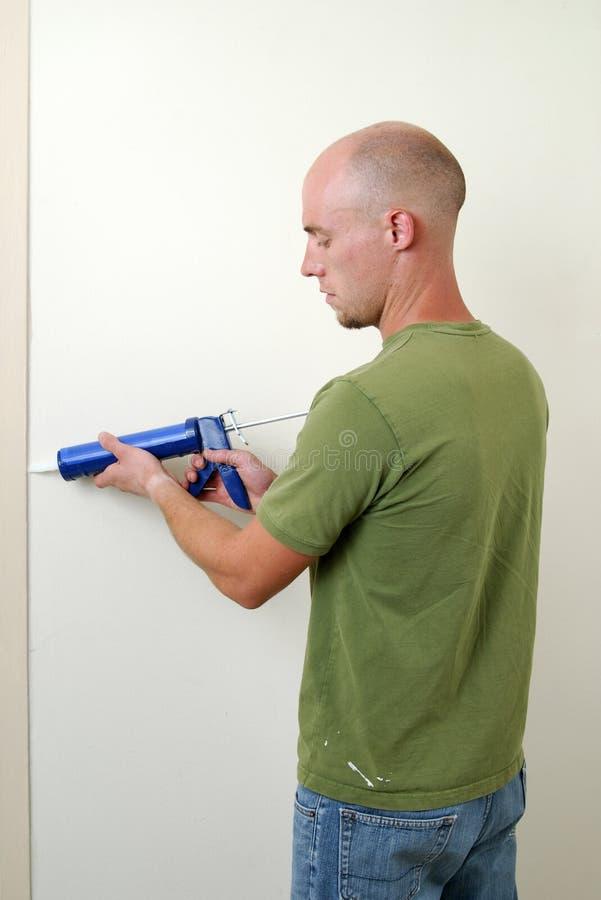 Uomo che calafata una porta fotografia stock