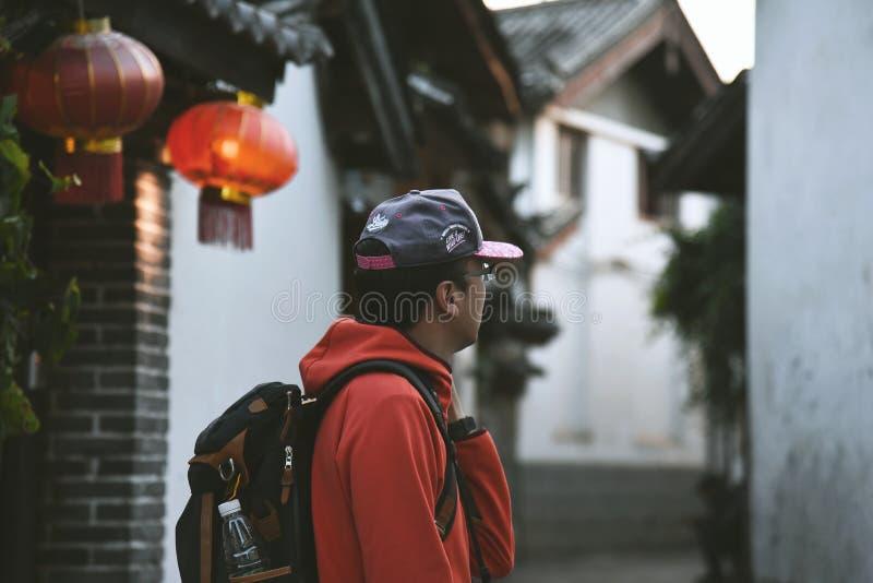 Uomo che cammina alla vecchia città di Lijiang fotografie stock libere da diritti