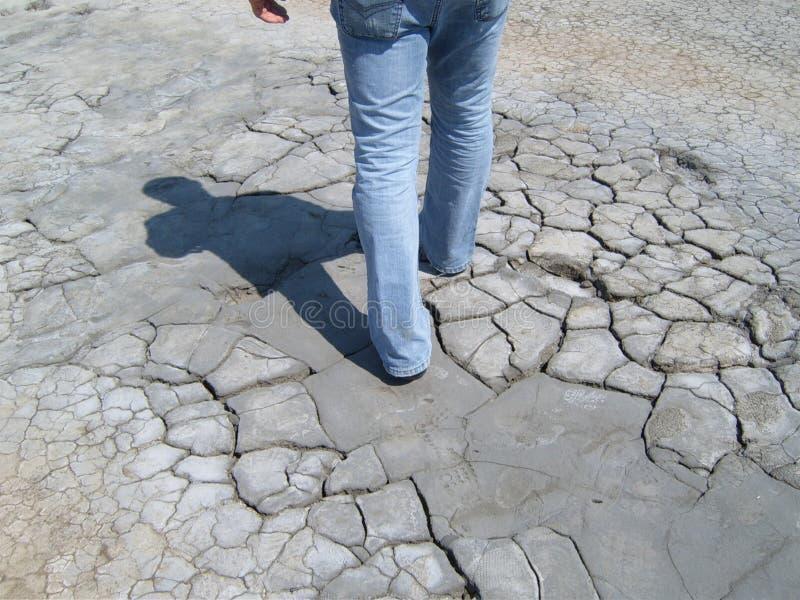 Uomo che cammina attraverso il deserto fotografia stock