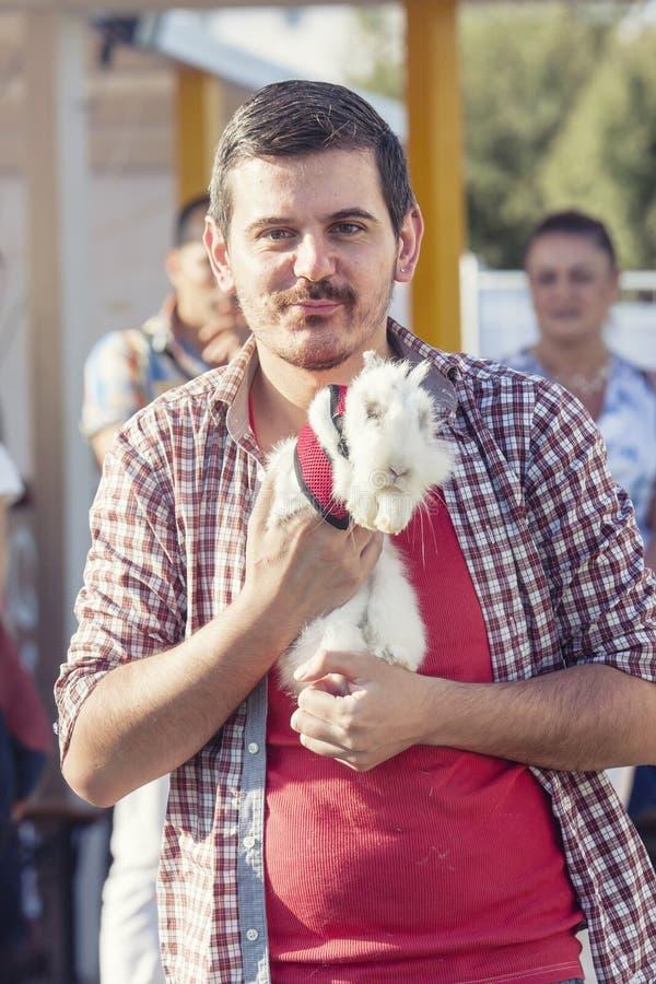 Uomo che cammina con il suo coniglio bianco dolce immagine stock