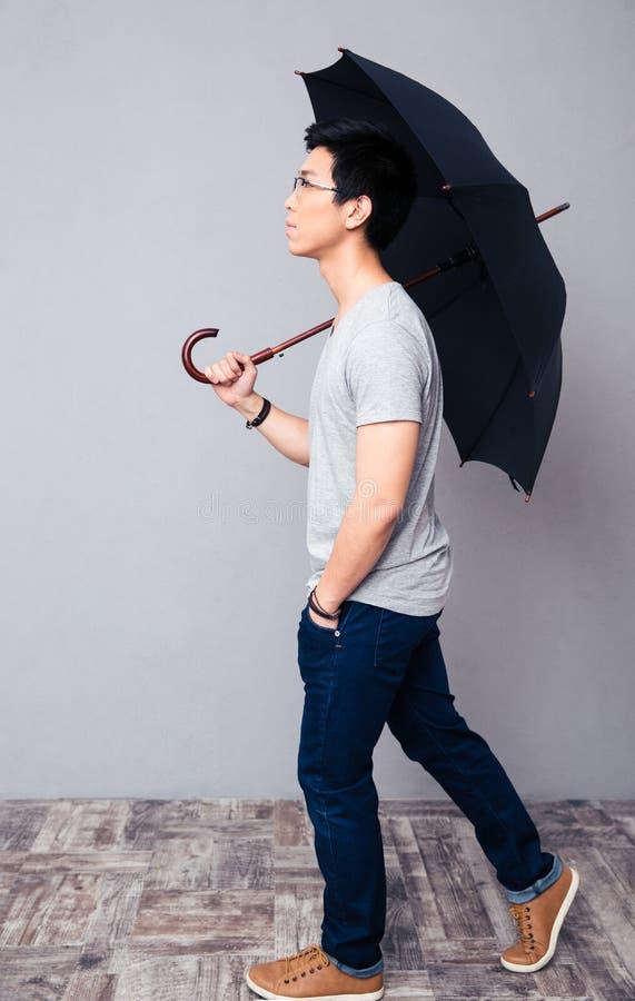 Uomo che cammina con l'ombrello fotografia stock