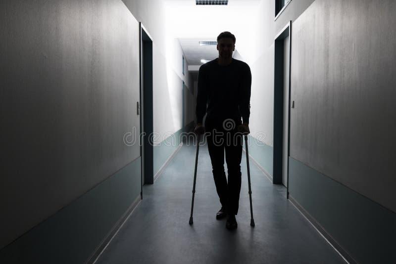 Uomo che cammina con le grucce fotografie stock libere da diritti