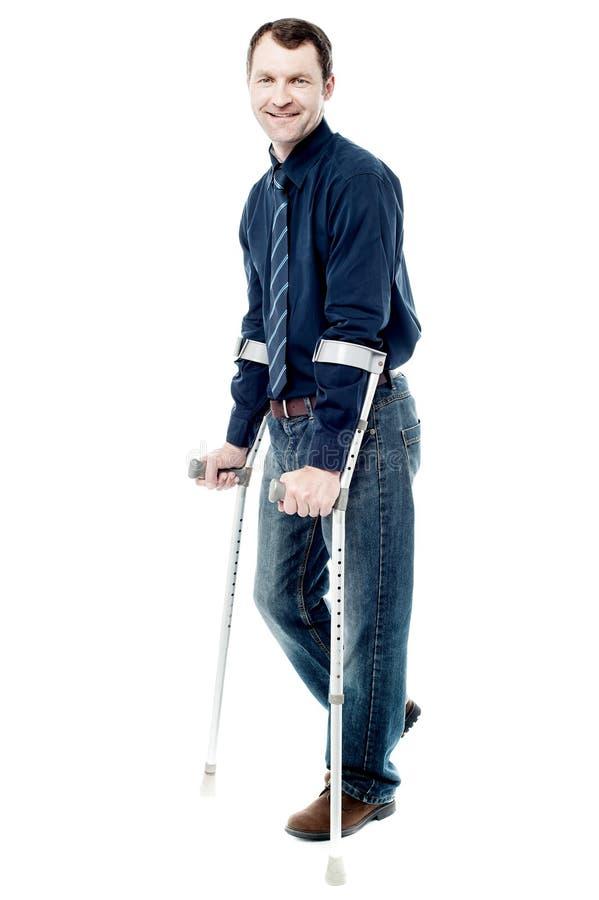Uomo che cammina con le grucce isolate su bianco fotografie stock libere da diritti
