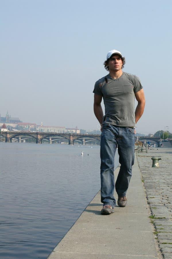 Uomo che cammina lungo l'argine fotografia stock libera da diritti