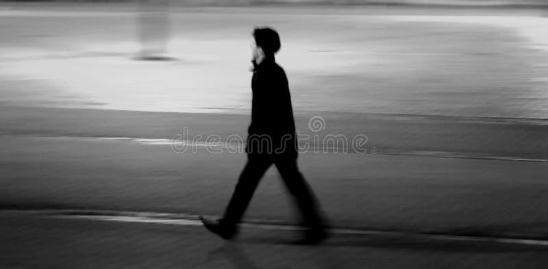 Uomo che cammina sopra la pavimentazione del cobblestone fotografia stock libera da diritti