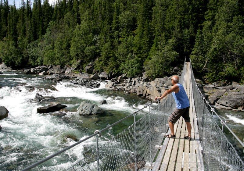 Uomo che cammina sopra un ponte sospeso immagini stock libere da diritti