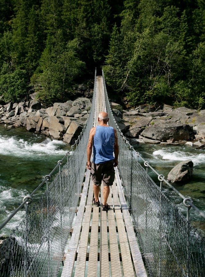 Uomo che cammina sopra un ponte sospeso fotografia stock libera da diritti
