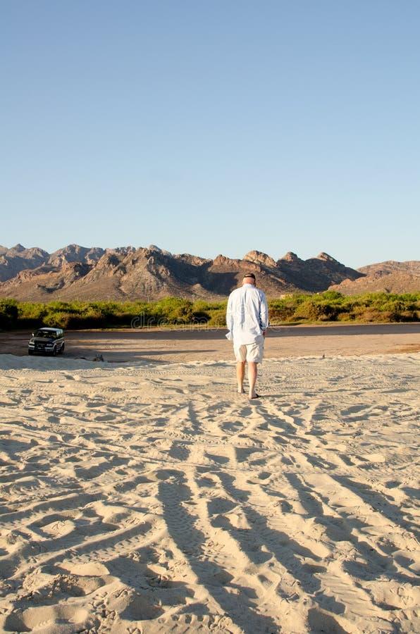 Uomo che cammina sulla sabbia in deserto immagine stock libera da diritti