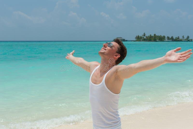 Uomo che cammina sulla spiaggia con a braccia aperte immagine stock libera da diritti