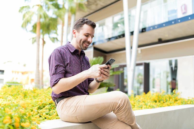 Uomo che cerca i caffè ed i ristoranti nell'applicazione su Pho mobile immagine stock