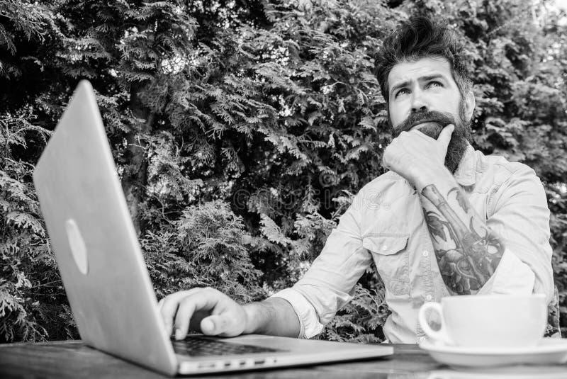 Uomo che cerca ispirazione Trovi l'argomento per scrivere Internet praticante il surfing del computer portatile barbuto dei panta immagini stock