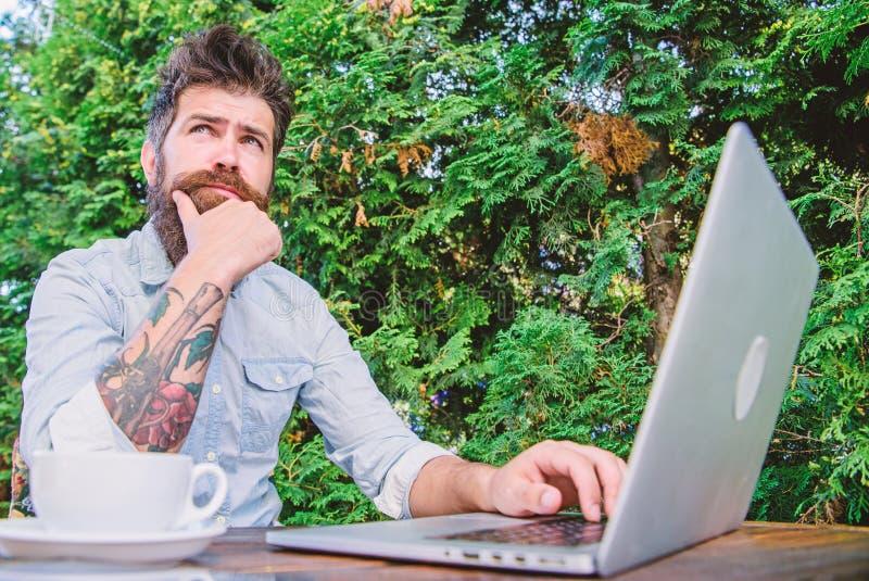 Uomo che cerca ispirazione Trovi l'argomento per scrivere Internet praticante il surfing del computer portatile barbuto dei panta immagine stock