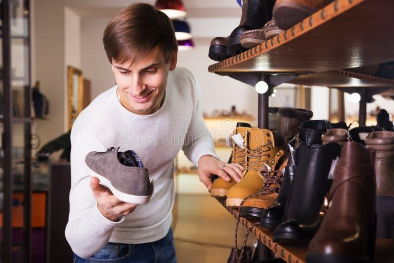 Uomo che cerca le scarpe di un winer in centro commerciale immagine stock