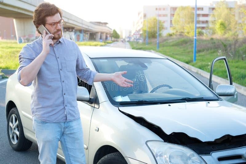 Uomo che chiama aiuto dopo l'incidente di incidente stradale sulla strada fotografie stock