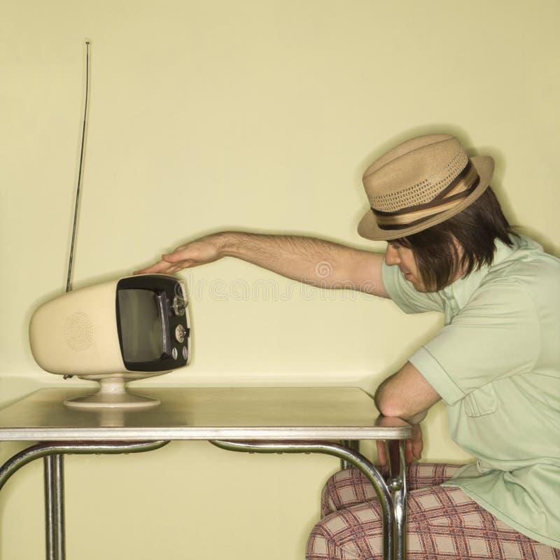 Uomo che colpisce vecchia televisione leggermente. fotografia stock libera da diritti