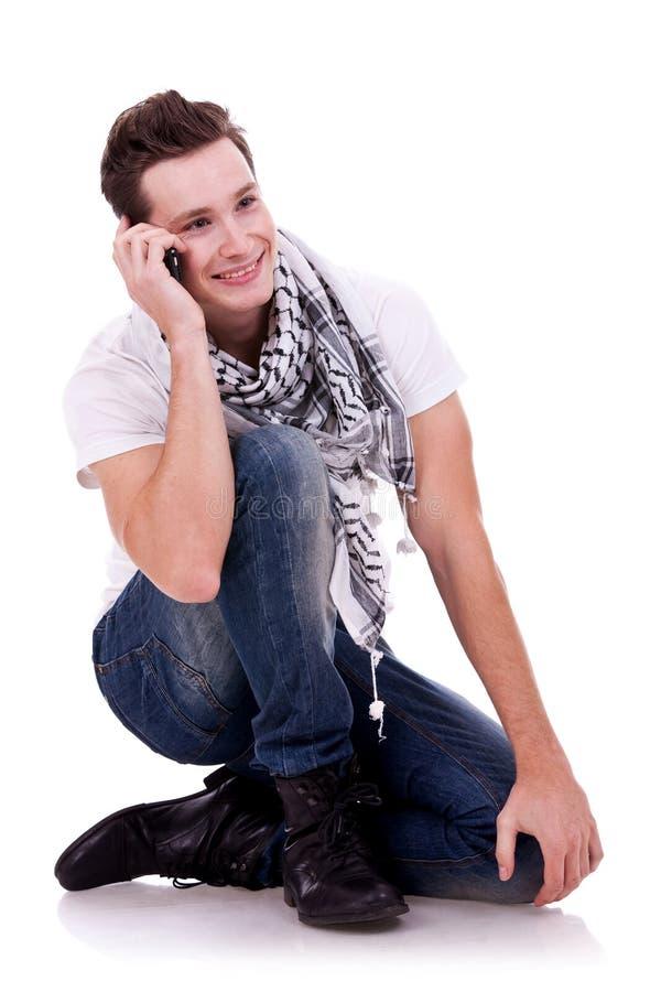 Uomo che comunica sul telefono mentre sedendosi immagine stock libera da diritti