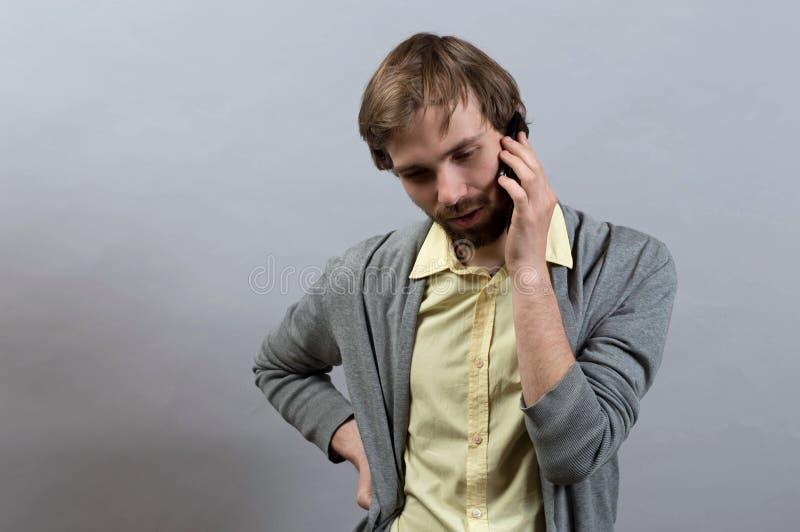 Uomo che comunica sul telefono Su un gray fotografia stock libera da diritti