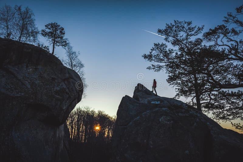 Uomo che considera condizione di alba sulla cima della roccia immagine stock