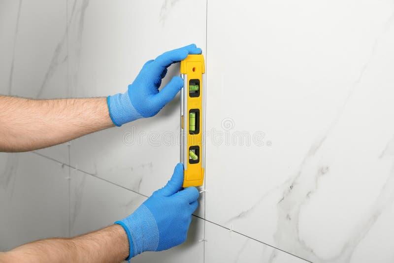 Uomo che controlla l'installazione adeguata della piastrella di ceramica con il livello sulla parete Costruzione e lavori di rist fotografie stock