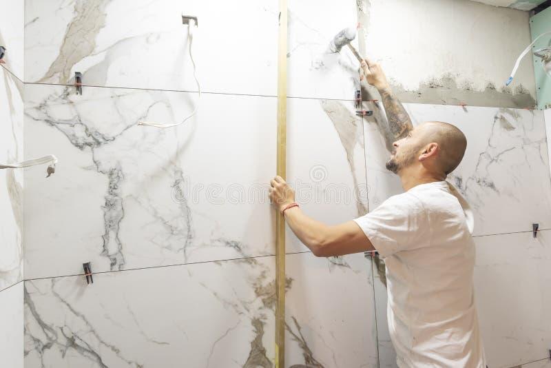 Uomo che controlla l'installazione adeguata della piastrella di ceramica con il livello sulla parete, primo piano Costruzione e l fotografie stock