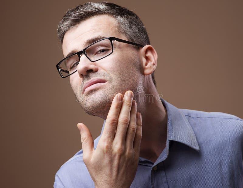 Uomo che controlla la sue barba e pelle immagine stock