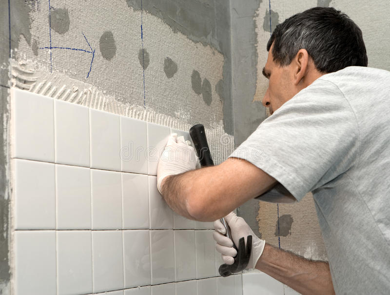Uomo che copre di tegoli una parete immagine stock