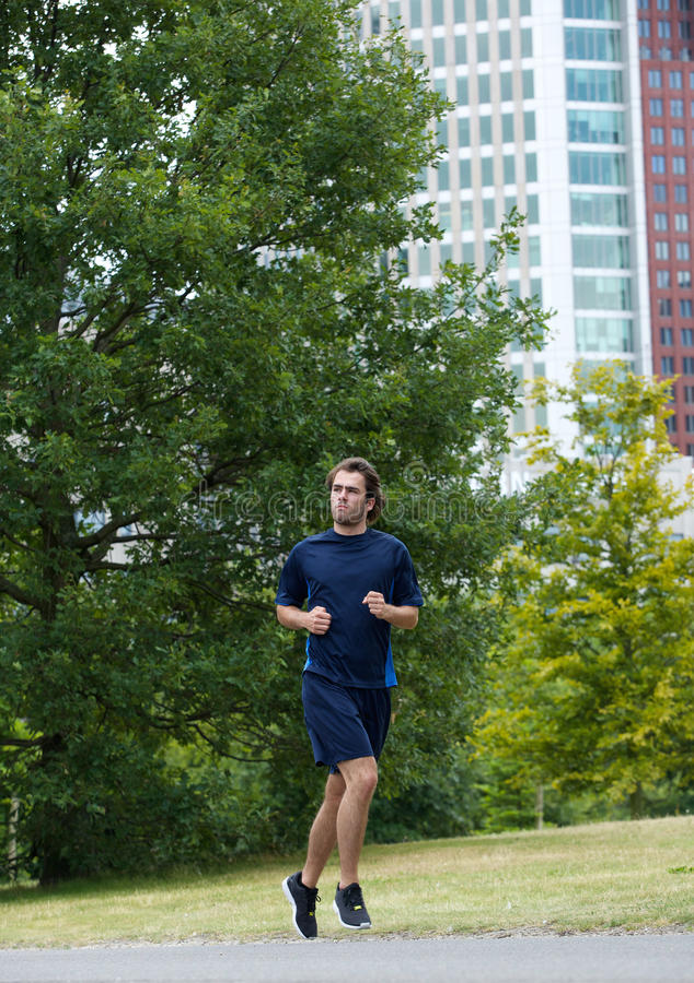 Uomo che corre all'aperto nel parco della città fotografia stock