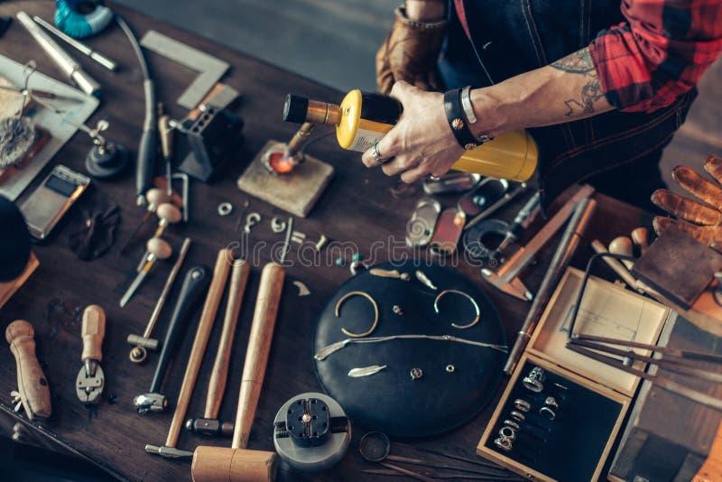 Uomo che crea i gioielli all'officina fotografia stock libera da diritti