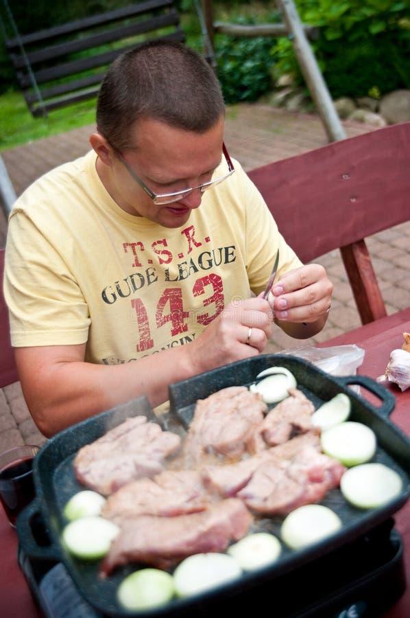 Uomo che cucina all'aperto fotografia stock