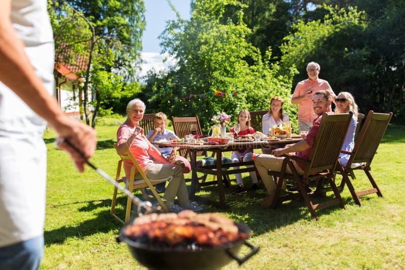 Uomo che cucina carne sulla griglia del barbecue al partito di estate fotografia stock libera da diritti