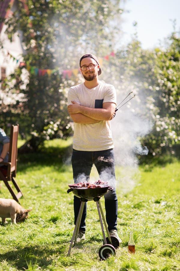 Uomo che cucina carne sulla griglia del barbecue al partito di estate immagini stock libere da diritti
