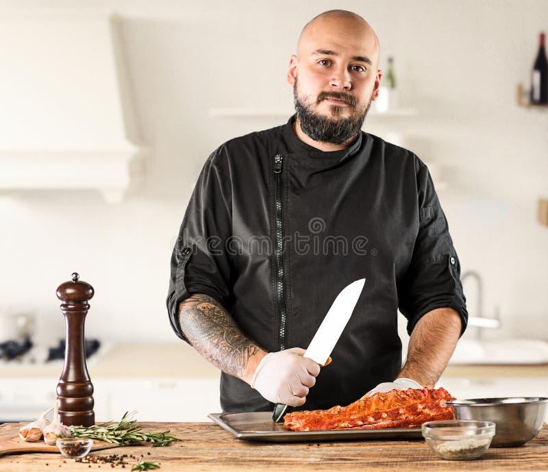 Uomo che cucina la bistecca della carne sulla cucina fotografia stock libera da diritti
