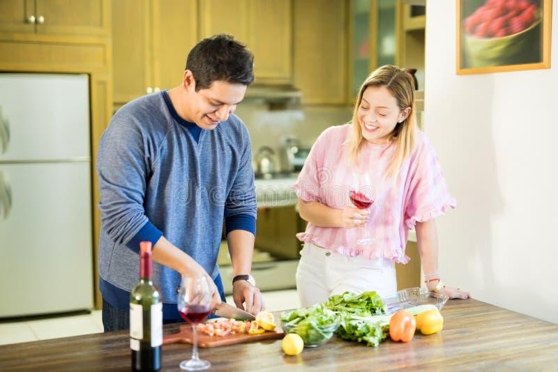 Uomo che cucina nella cucina con l'amica fotografie stock